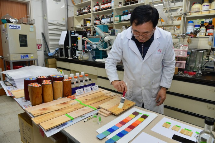 남기달 KIST 책임연구원이 나무에 명유를 바르고 있다. 현대 기술을 적용해 재탄생한 명유는 들기름 외 다른 물질이 첨가되지 않아 전통방식으로 제작했을 때보다 색이 맑다. - KIST 제공